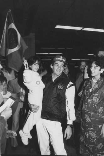 Ao lado de sua irmã Viviane, Senna ergue criança com bandeira no colo na chegada ao Brasil em 1985