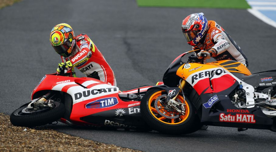 Valentino Rossi (esquerda) e Casey Stoner tentam levantar as motos aps acidente entre os dois pilotos. Stoner teve que abandonar a prova GP de Jerez de la Frontera