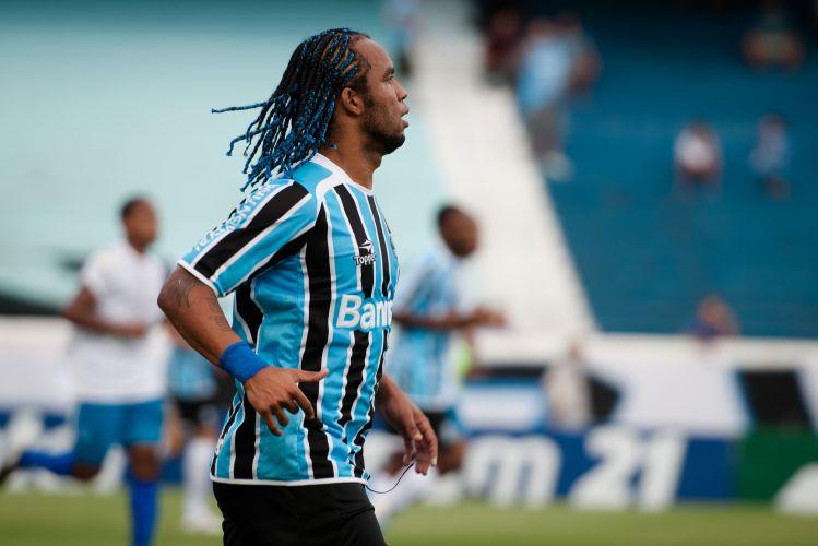 Carlos Alberto em ação pelo Grêmio contra o Cruzeiro-RS. O meio-campista, capitão do time, estreia trancinhas azuis em homenagem à sua equipe.