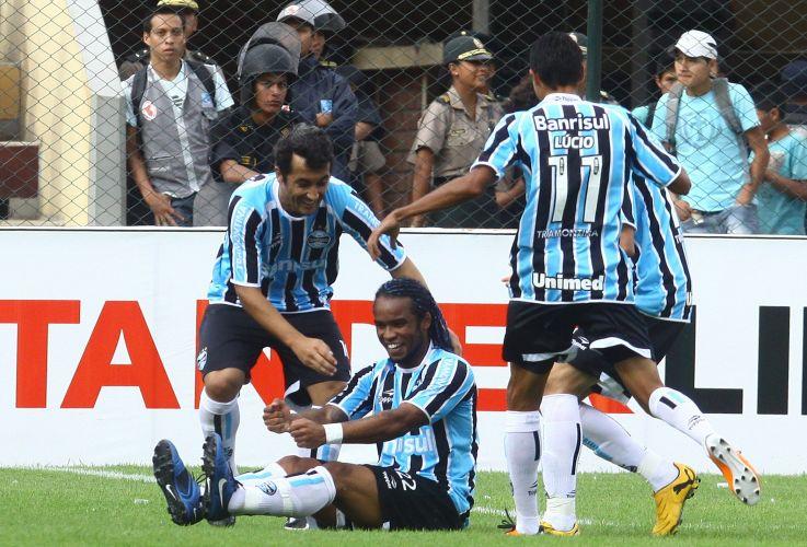 Provocando o Inter, Carlos Alberto relembra a derrota do rival para Mazembe e comemora como o goleiro Kidiaba; o Grêmio empatou em 1 a 1 com o León, no Peru, e adiou sua classificação na Libertadores