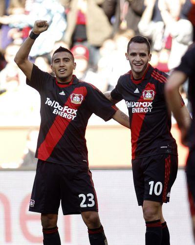 Arturo Vidal e o meia brasileiro Renato Augusto (d) comemoram um dos gols da vitória por 2 a 0 do Bayer Leverkusen sobre o Schalke 04. Com o resultado, time reduziu para sete pontos a distância para o Borussia Dortmund, líder do Campeonato Alemão