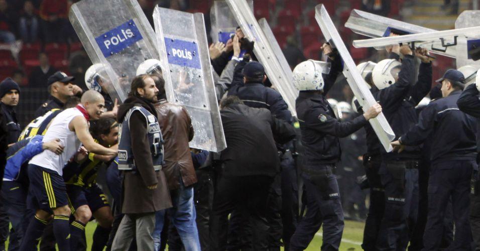 Jogadores do Fenerbahce são protegidos pela polícia de objetos atirados pela torcida do Galatasaray em clássico do futebol turco