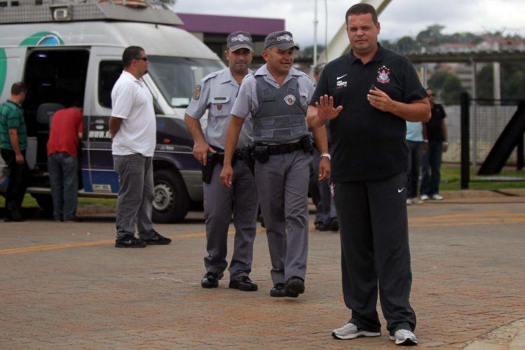 Segurança do Corinthians acena para a câmera ladeado de policiais, que terão pouco trabalho. A apresentação de Adriano reuniu menos pessoas que o esperado no CT do Parque Ecológico.