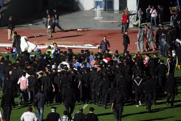 Centanas de policiais entram em campo e têm trabalho para conter a multidão. A principal preocupação foi proteger o árbitro