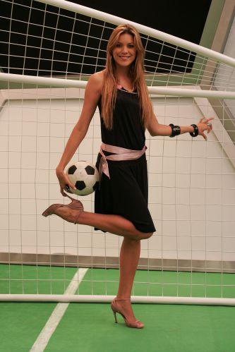 Loira posa com bola de futebol.
