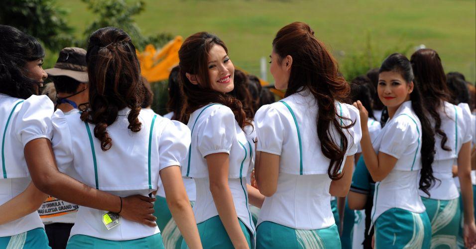 Grid girls malaias caminham após sessão de fotos antes da largada para o Grande Prêmio da Malásia em Sepang