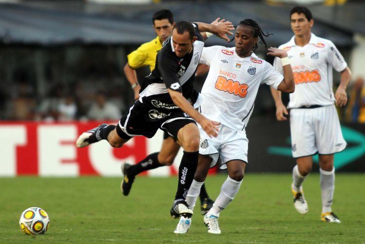 Com o árbitro ao fundo, Arouca, do Santos, diz não ter cometido falta sobre o atacante da Ponte Preta, no jogo válido pelas quartas do Campeonato Paulista.