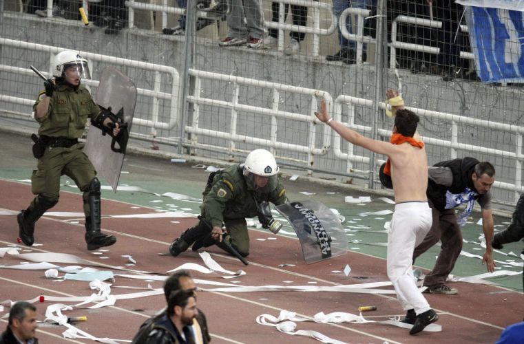 Torcedor pede calma enquanto um policial tropeça durante um confronto na Grécia. O episódio violento aconteceu após a final da Copa da Grécia, conquistada pelo AEK.