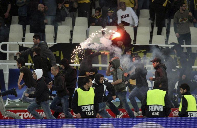 Torcedor do AEK exibe um sinalizador na arquibancada do estádio Olímpico de Atenas. Após o time vencer a Copa da Grécia, fãs atiraram objetos e invadiram o gramado, gerando uma confusão generalizada com a polícia.