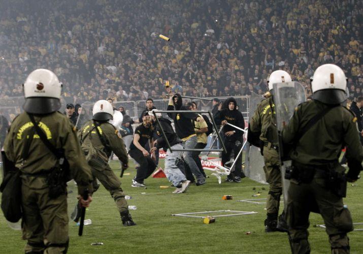 Torcedores usam grades de ferro para atacar a policia durante o confronto que se seguiu à final da Copa da Grécia, vencida pelo AEK.