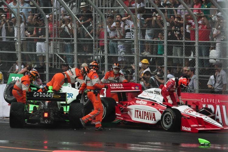 Pilotos deixam seus carros após uma batida logo no início da prova da Fórmula Indy em São Paulo, marcada por muita chuva e até raios.
