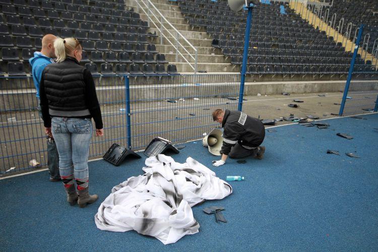 Oficiais da polícia avaliam o prejuízo no estádio após conflitos com hooligans. Garrafas de vodka, proibidas dentro em jogos de futebol, foram encontradas no local