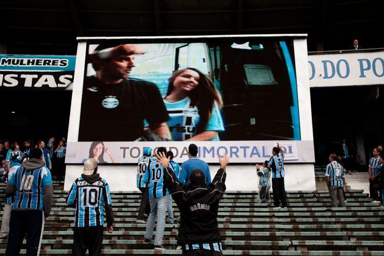 Torcida do Grêmio aplaude Renato Gaúcho. No telão do estádio Olímpico, a imagem do técnico gremista chegando para a final do Gauchão de mãos dadas com a filha.