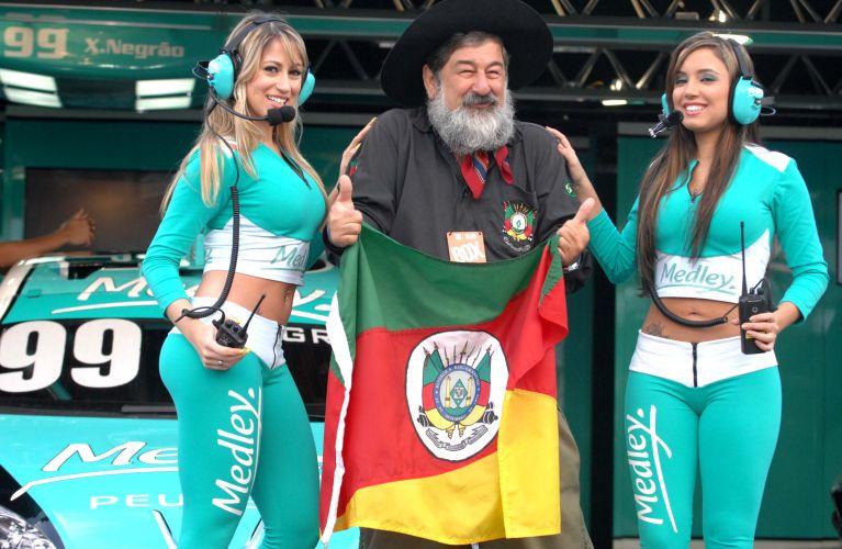 Primas Carolina (esquerda) e Daniela (direita) posam com gaúcho vestido de roupas típicas durante etapa da Stock Car.