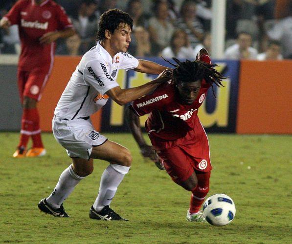 Tinga (d) tenta girar e se livrar da marcação santista na estreia do Inter no Brasileirão contra os reservas do Santos na Vila Belmiro