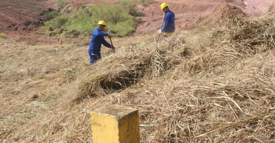 Operários limpam a área onde estão enterrados os dutos da Petrobras no terreno onde será construído o estádio do Corinthians em Itaquera; tubos serão desviados para não comprometer a obra