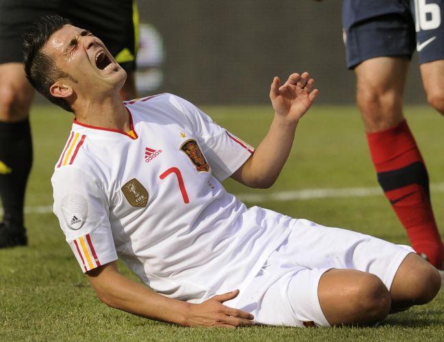 O atacante espanhol David Villa grita de dor após receber falta