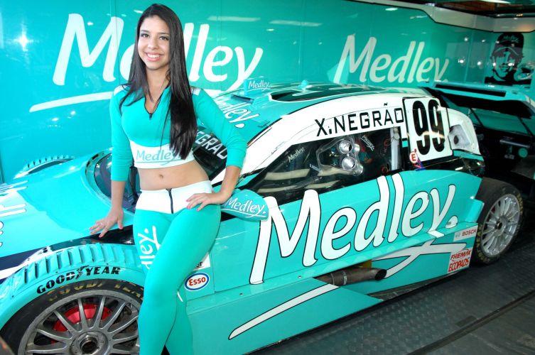 Modelo posa para foto ao lado do carro de Xandinho Negrão, antes da prova da Stock Car em Campo Grande