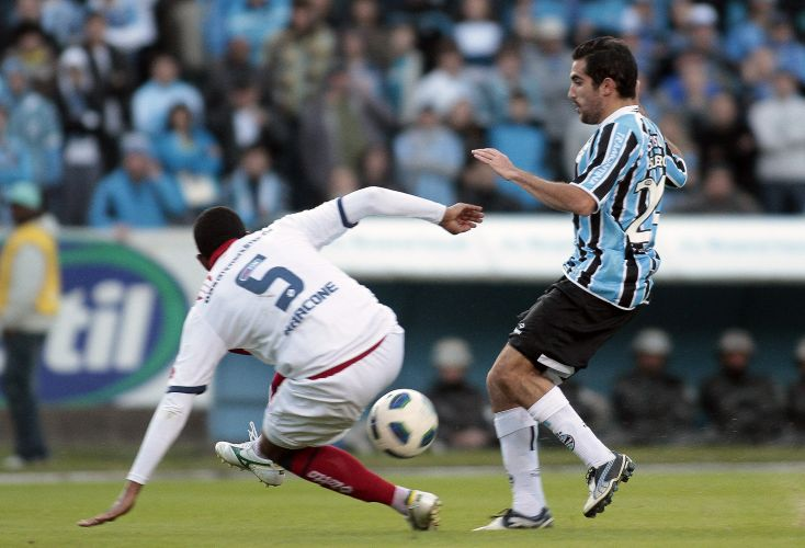 Escudeiro, do Grêmio, divide bola com marcador do Bahia