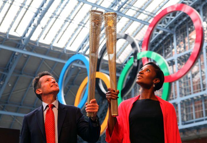 Sebastian Coe(esq.), presidente do Comitê Organizador dos Jogos, posa com a tocha ao lado da ex-atleta britânica Denise Lewis