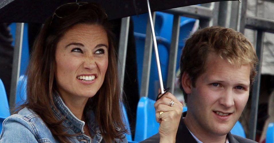 Pippa Middleton, irmã da duquesa britânica Kate, se protege da água com guarda-chuva em Londres durante o Torneio de Queen's