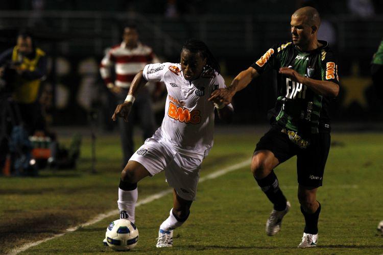 Santista Arouca (e) parte com a bola na partida contra o América-MG no Pacaembu
