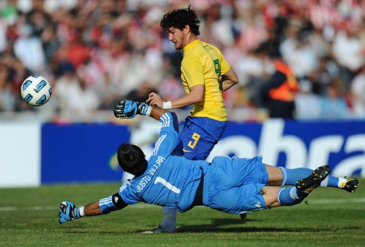 Alexandre Pato tenta tirar o goleiro Villar depois de receber nas costas da zaga paraguaia. O atacante chegou a driblar o goleiro, que se esticou e fez bonita defesa para impedir o gol.