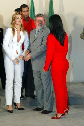 Sheila Mello (e) é recebida pelo então presidente Luiz Inácio Lula da Silva junto com a também dançarina Scheila Carvalho (de vermelho)