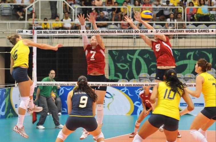 Brasileira Milchelle (e) encara bloqueio duplo dos Estados Unidos na vitória por 3 a 0 (25-4, 25-7 e 25-7) na estreia da equipe feminina no vôlei dos Jogos Mundiais Militares