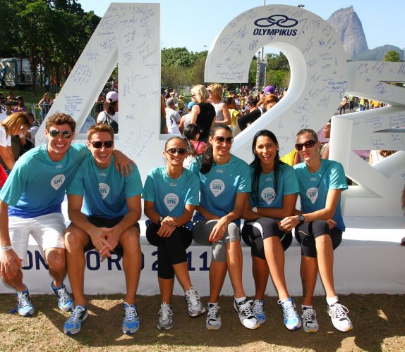 Estrelas da seleção brasileira de vôlei, jogadores Bruninho, Murilo, Fabi, Sheilla, Jaqueline e Mari (da esq. para a dir.) posam para foto na placa dos 42km da Maratona do Rio