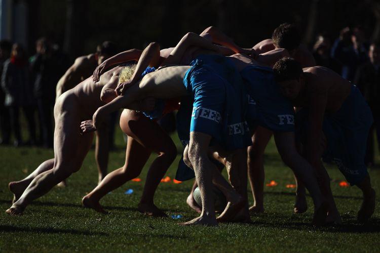 Jogadores pelados do Black Nudes e do combinado de Fiji fazem o scrum, movimento de reinício de jogo no rúgbi