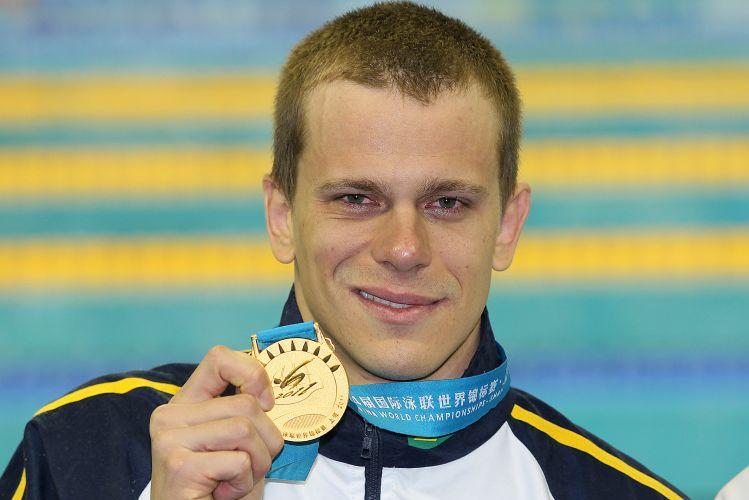 Ainda com os olhos vermelhos, Cesar Cielo sorri e exibe a medalha de ouro conquistada nos 50m borboleta no mundial de Xangai