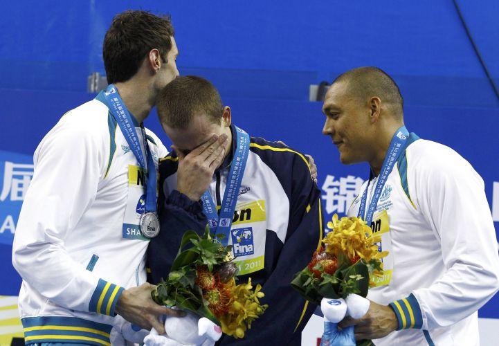 Os australianos Matthew Targett (à esquerda) e Geoff Huegill, medalhas de prata e bronze respectivamente, consolam choro de emoção de Cesar Cielo após brasileiro conquistar o ouro na China