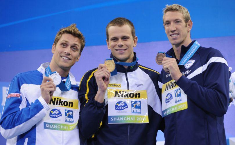 Cesar Cielo (c) exibe a medalha de ouro conquistada nos 50m livres no Mundial de Esportes Aquáticos em Xangai (China). O italiano Luca Dotto (e) levou a prata; o francês Alain Bernard (d) conquistou o bronze