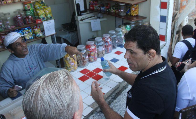 Minotauro faz intervalo na visita ao Morro do Cantagalo para comprar garrafa de água. Lutadores de MMA visitaram comunidade carioca nesta terça-feira