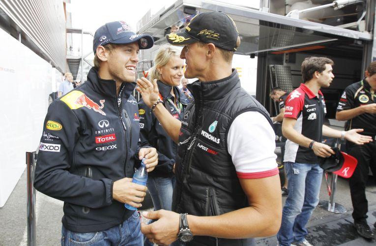 O alemão Sebastian Vettel cumprimenta o compatriota Michael Schumacher, que completa 20 anos de sua estreia na Fórmula 1