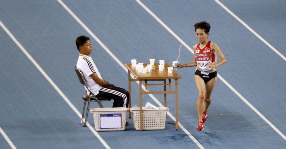 A japonesa Megumi Kinukawa aproveita para se hidratar durante a prova dos 10 mil metros no Mundial de Daegu, da Coreia do Sul