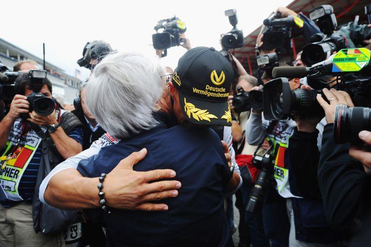 Michael Schumacher recebe abraçado de Bernie Ecclestone, chefão da Fórmula 1. Piloto alemão comemora 20 anos de sua estreia na Fórmula 1