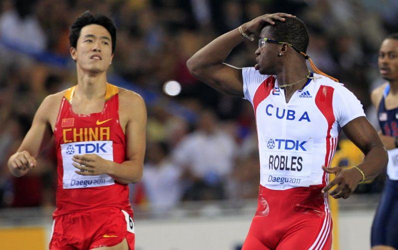 O cubano Dayron Robles reage após conquistar a medalha de ouro nos 110 m com barreiras, enquanto é observado pelo chinês Liu Xiang. Porém, pouco tempo depois, o cubano foi desclassificado pela organização da prova e perdeu o título de campeão mundial
