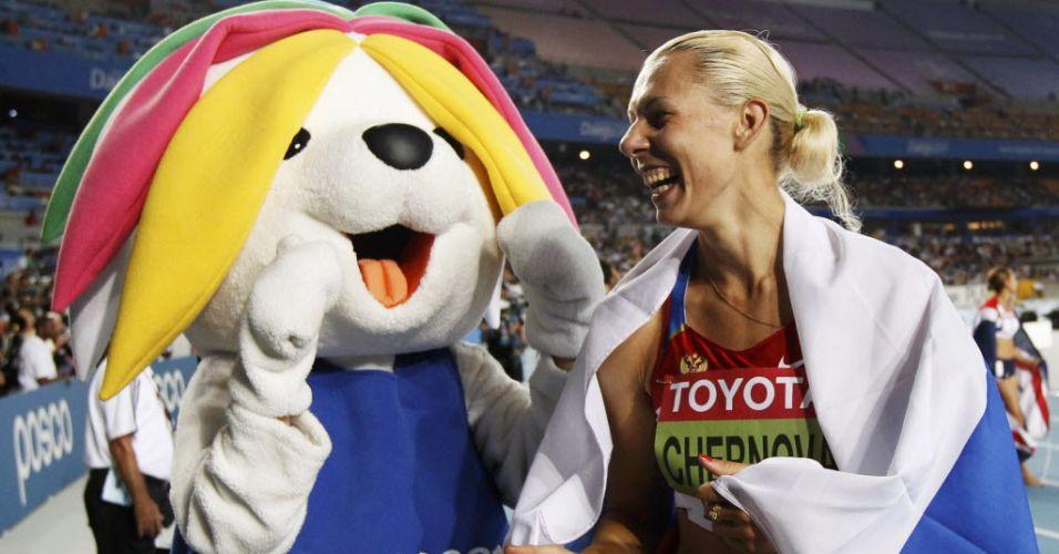 A russa Tatyana Chernova, que ganhou o heptatlo, posa para fotos com a mascote oficial do Mundial de atletismo em daegu, na Coreia do Sul.
