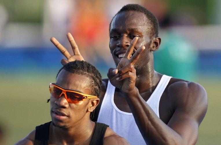 Descontraído, Usain Bolt faz chifrinhos em seu amigo e rival Yohan Blake, também jamaicano, que venceu os 100m depois de Bolt ser eliminado.