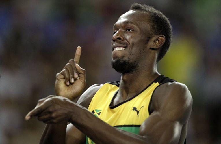 Usain Bolt sorri para as câmeras após vencer a sua bateria na semifinal dos 200m no Mundial de atletismo em Daegu.