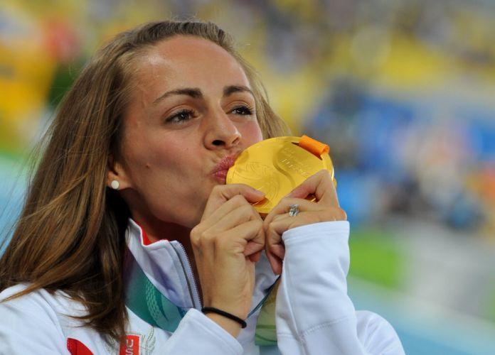 A norte-americana Jennifer Barringer Simpson, que venceu os 1.500m na última quinta, recebe e beija sua medalha de ouro em Daegu.