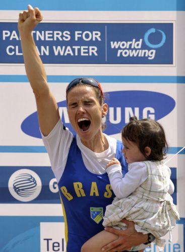 Fabiana Beltrame comemora no pódio com a filha Alice após conquistar a medalha de ouro no Mundial de remo