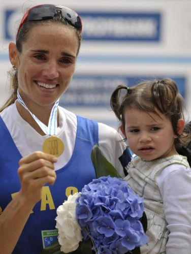 Com a filha Alice no colo, Fabiana Beltrame exibe a medalha de ouro conquistada no Mundial de remo