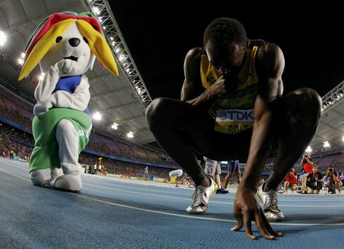 Ao lado da mascote Sarbi, Usain Bolt se abaixa na pista depois de vencer os 200 m rasos em Daegu