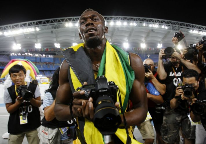 Jamaicano Usain Bolt pega cmera fotogrfica aps vencer os 200 m rasos