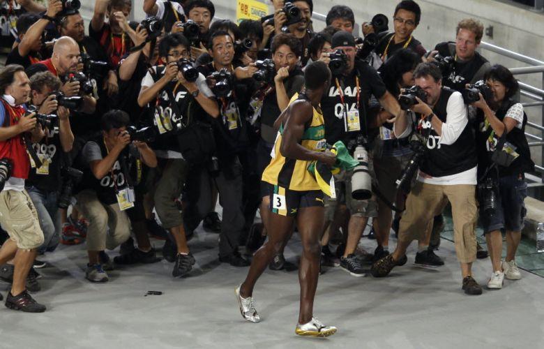 Usain Bolt brinca com os fotógrafos correndo de um lado para o outro depois de vencer os 200 m rasos em Daegu