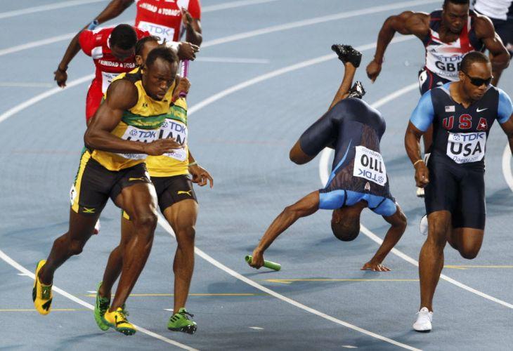 Usain Bolt dispara ao receber bastão de Yohan Blake, enquanto Darvis Patton cai na pista e elimina a equipe dos Estados Unidos quando tentava passar o bastão para Walter Dix