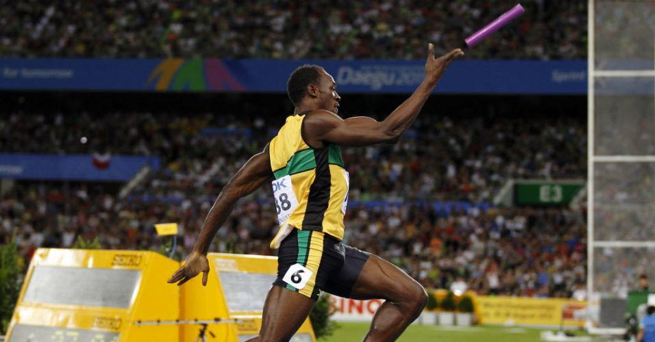 Usaib Bolt lança bastão depois de cruzar a linha de chegada na primeira posição no revezamento